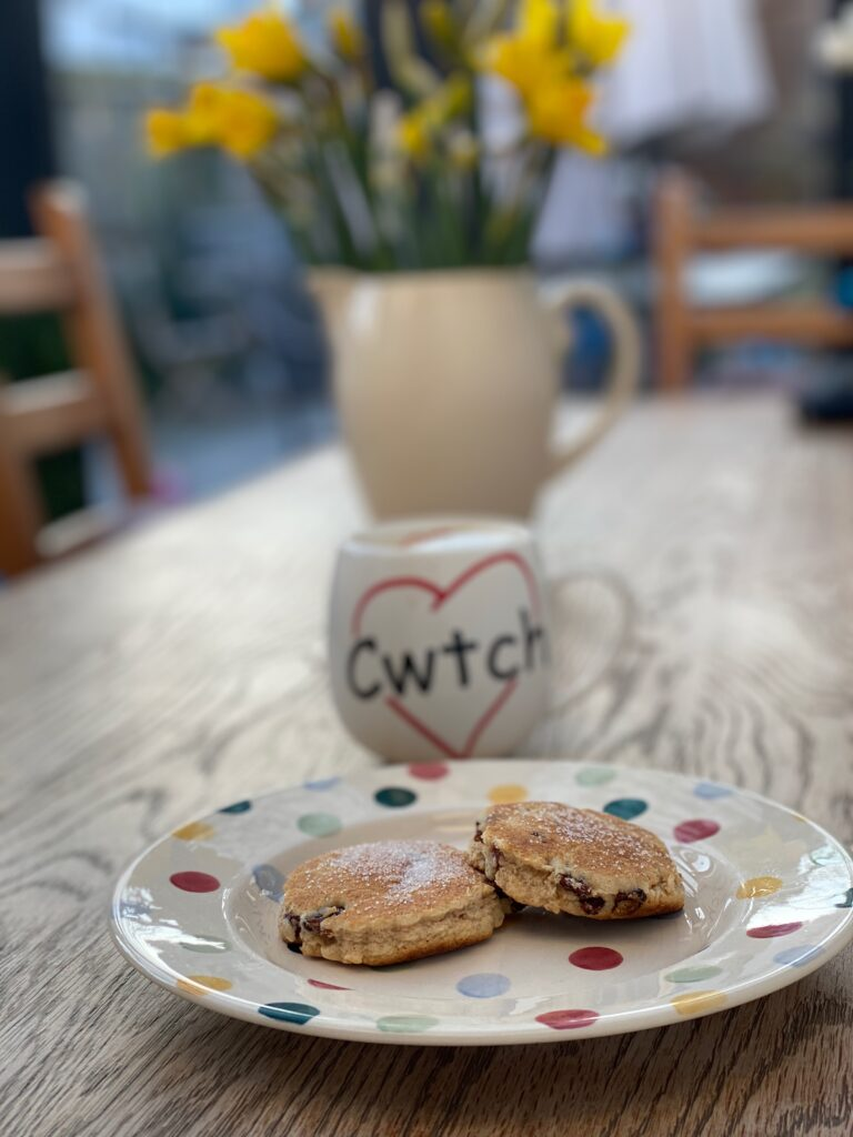 Traditional welsh cakes on a plate with daffodils